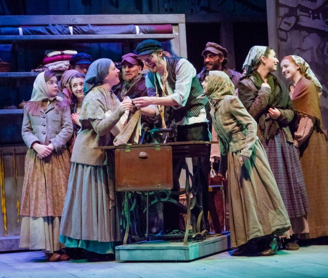 "Motel (Alex Brick) Shows Off His New Sewing Machine to Tzeitel (Rachel Holmes) and other villagers in the 2014 production of ""Fiddler on the Roof"" done by Children's Theater of Madison (2014)<br>Photo Credit: Tom Klingele"